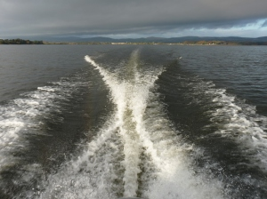 The boat cuts a line through the water as it crosses the loch