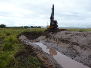 A digger working on creating a drainage ditch