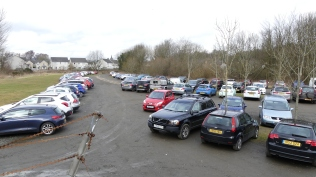 A busy car park with the walkathon on a sunny day